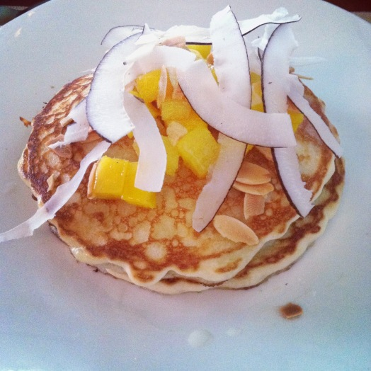 Gluten-free pancakes served with almonds, mango and coconut.